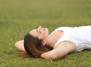 Mulher-deitada-na-grama-descansando-para-aumentar-produtividade
