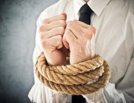 Businessman with hands tied in ropes. Business problems and difficulties, obstructions and limits in work.